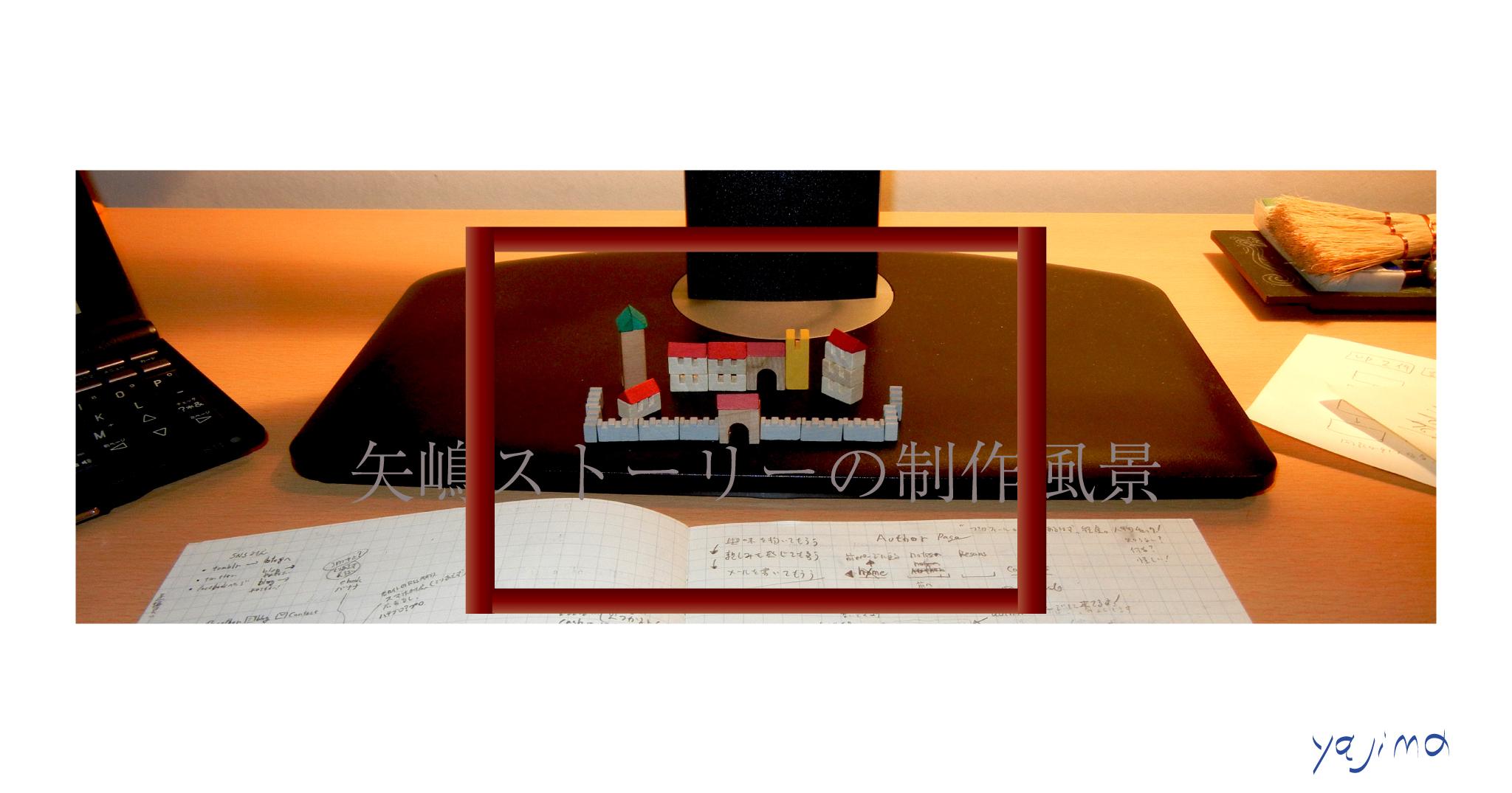 木枠の額縁の中に「矢嶋ストーリーの制作風景」の文字。その後ろに小さな積み木。中世の街の風景。